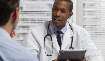 doctor holding tablet speaking with patient